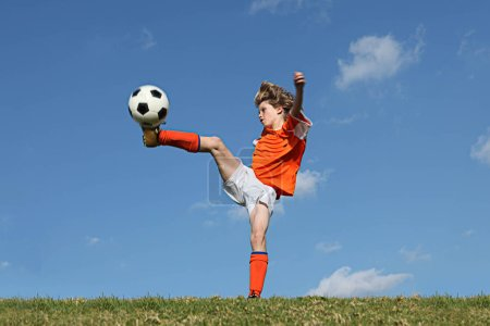 Photo for Kid playing football or soccer kicking ball - Royalty Free Image