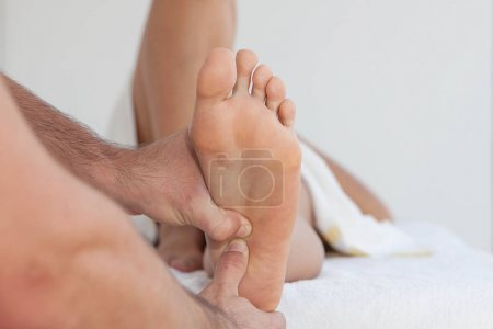 Photo for Masseur giving therapeutic foot massage - Royalty Free Image