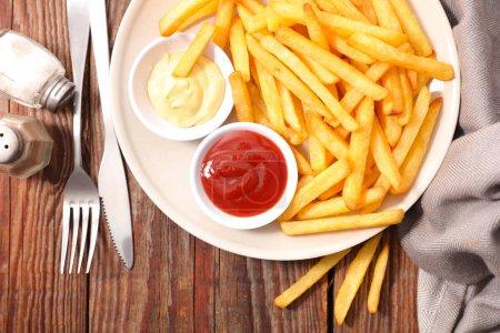 Photo pour Français des frites avec du ketchup sur fond en bois - image libre de droit