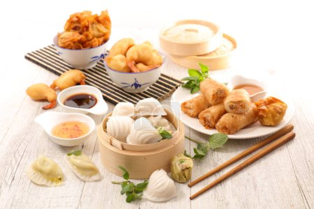 Photo for Variety of asian cuisine, spring rolls, dumplings on wooden table - Royalty Free Image