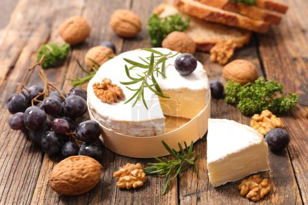 Camembert with walnuts and olives on wooden backgr...
