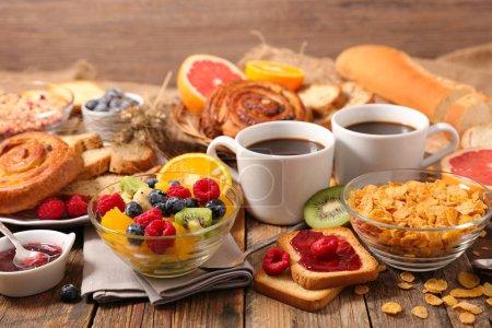 Photo pour Petit déjeuner avec fruits, flocons de maïs, tasse de café - image libre de droit