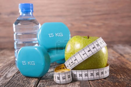 apple,water and dumbbell on wooden table