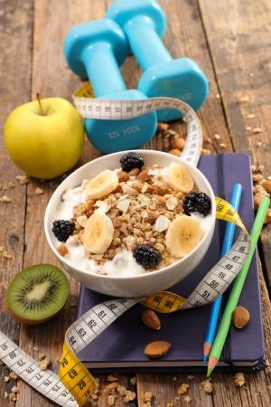 Photo for Granola with fruits and dumbbells on wooden table, healthy food concept - Royalty Free Image