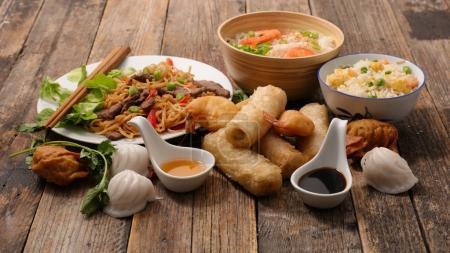 Photo pour Assortiment de nourriture chinoise, nouilles, riz, rouleaux de printemps crevettes et sauces sur table en bois - image libre de droit