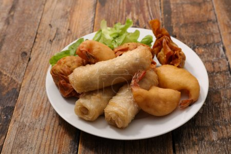 spring roll and fried shrimps on wooden table