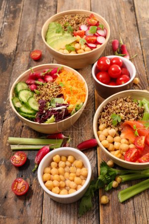 different sorts of  buddha bowls on wooden table, trendy vegetarian salads