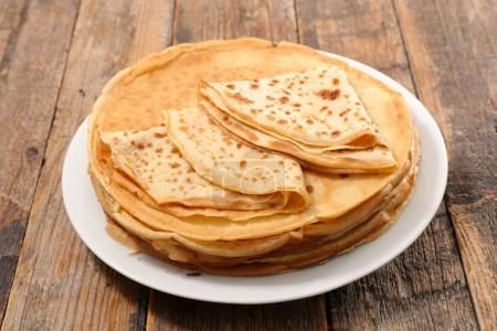 White plate with crepes on wooden table...