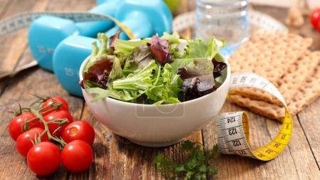 bowl with salad and water bottle with measuring tape and dumbbells, sport and healthy food concept