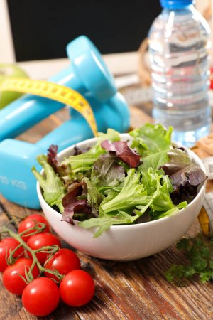 Photo for Bowl with salad and water bottle with measuring tape and dumbbells, sport and healthy food concept - Royalty Free Image