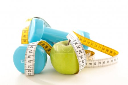 apple with dumbbells and measuring tape, sport and diet concept