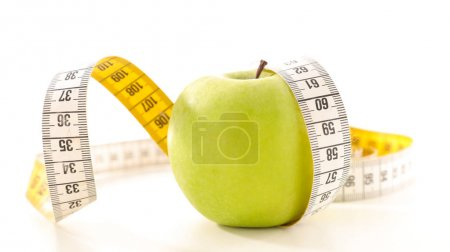 apple and measuring tape isolated on white background, diet concept