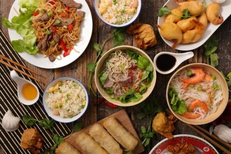 Photo for Bowls of assorted asian dishes on wooden table - Royalty Free Image