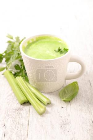 cup with vegetable detox drink on wooden table