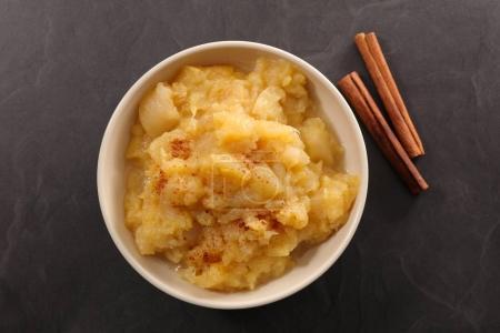 white bowl with apple flesh and cinnamon sticks