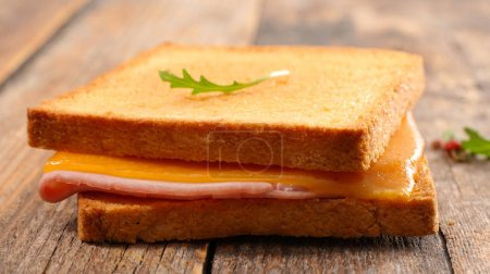 Grilled toast with ham and cheddar on wooden table
