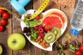 Healthy food concept with fruit plate and centimeter tape on wooden table