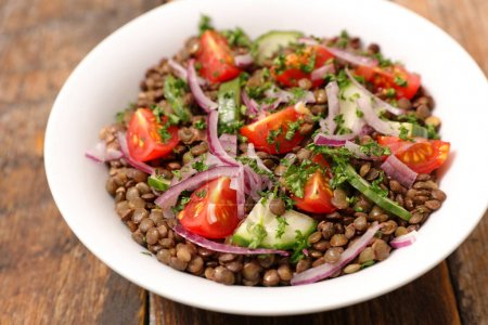 Photo for Bowl of lentils salad served on white plate. - Royalty Free Image