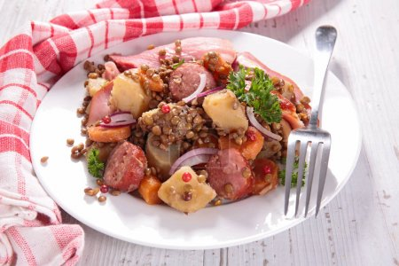 Lentils with meat and vegetables served on white plate.