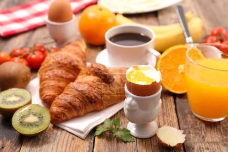 Breakfast with soft-boiled egg, croissants, coffee and fresh fruits on wooden table