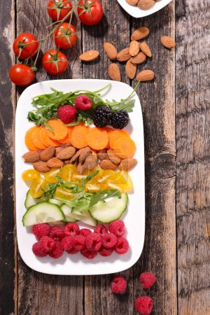 assorted berries with almonds and vegetables on white plate, healthy eating concept