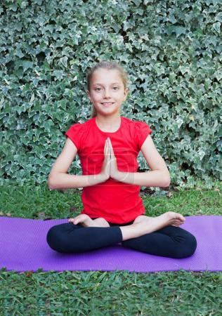 Photo for Little girl doing yoga exercise with mat legs and body bending - Royalty Free Image