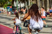 Brazilian daughter and mother riding on the bicycles by bicycle lane in Copacabana, Rio de Janeiro, Brazil