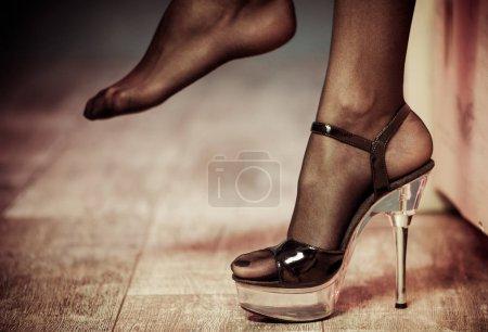 Photo pour Pieds sexy en bas et talon haut gros plan sur le sol en bois - image libre de droit