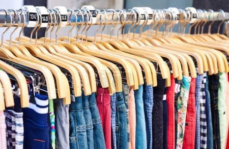 Photo pour Vêtements décontractés multicolores sur cintres en bois dans le magasin - image libre de droit