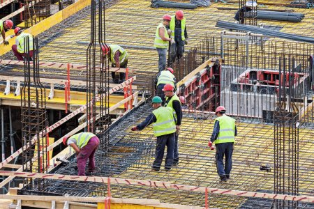Photo for Vilnius, Lithuania - September 01, 2017: Group of men workers working at the construction site in Vilnius, Lithuania - Royalty Free Image