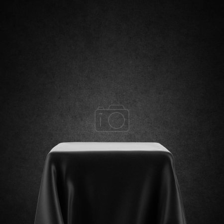 Photo for Black and white empty table, spotlight pedestal covered with cloth isolated on backlit background - Royalty Free Image