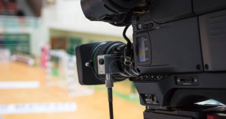 Camera ready to relay handball match. Blurred court background. Details of camera.