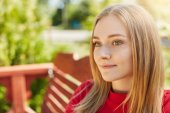 Pensive woman with sad appealing eyes, freckled pure skin, round face and blonde hair looking aside while sitting at bench in park analyzing what she done and dreaming about something good in her life