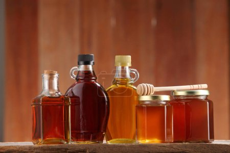Pure agave and maple syrups in bottles and honey i...