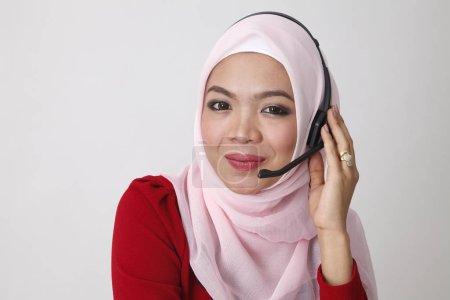 Photo pour Portrait de femme malaise dans des écouteurs travaillant à la réception - image libre de droit