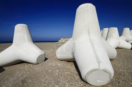 Italy, Sicily, Messina province, concrete tetrapods on the beach near a port under construction