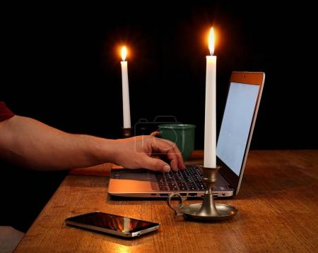 Home Office with Laptop Illuminated by Candlelight