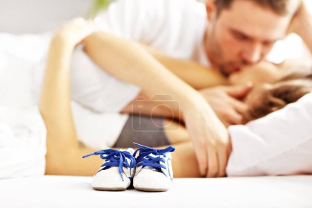 couple kissing in bed and baby shoes