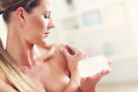 fit woman holding lotion