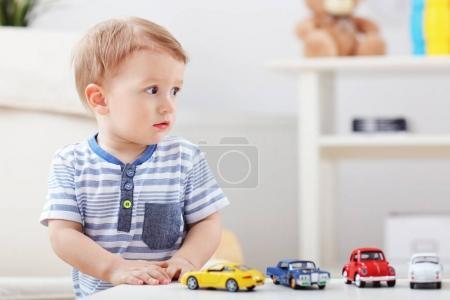 Photo pour Joyeux bébé garçon avec des jouets à la maison - image libre de droit