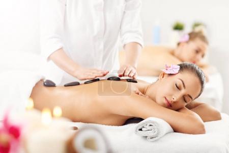 Photo pour Photo de deux belles femmes recevant le massage dans le spa - image libre de droit