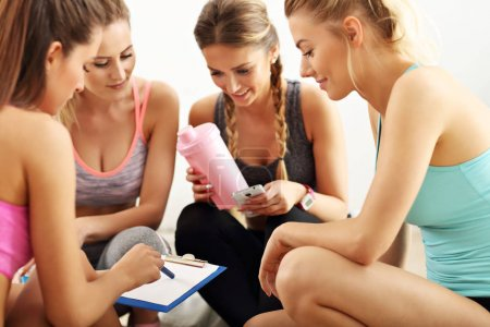 Photo for Picture showing young women group discussing workout plan at the gym - Royalty Free Image