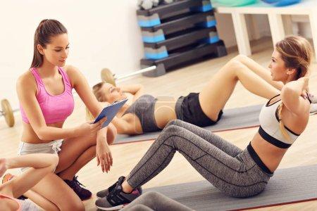Photo pour Photo montrant de jeunes femmes faisant des sit-ups dans une salle de gym - image libre de droit