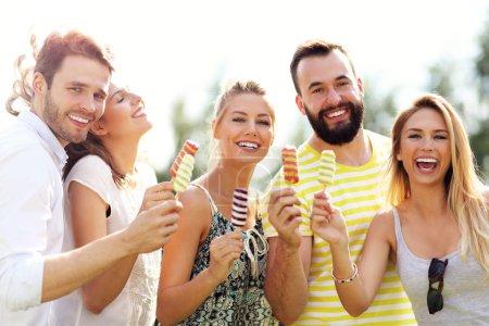 Photo pour Photo montrant un groupe d'amis mangeant de la glace à l'extérieur - image libre de droit