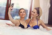 Happy girl friends enjoying jacuzzi in hotel spa