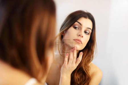 Young woman standing in bathroom in the morning