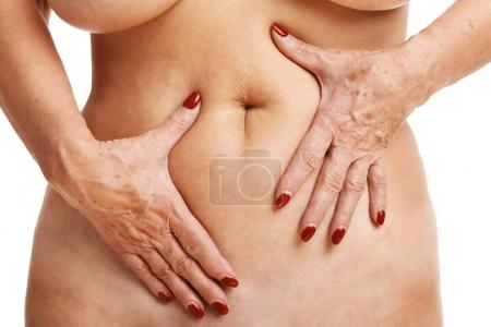 Senior woman touching abdomen over white background