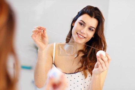 Photo pour Photo montrant une jeune femme regardant dans un miroir de salle de bain - image libre de droit