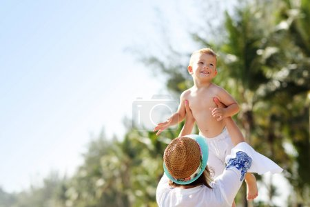Picture of mother having fun on the beach with her little son