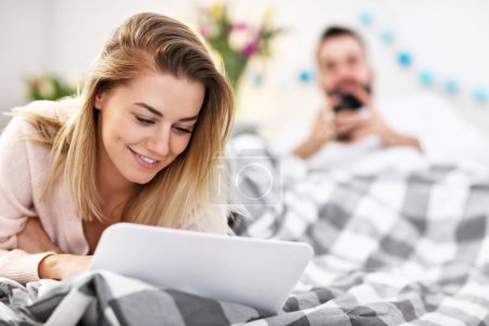 Adult couple with laptop computer in bed